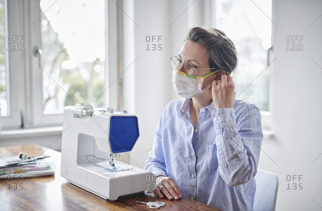 Woman trying face mask- she is sewing at home