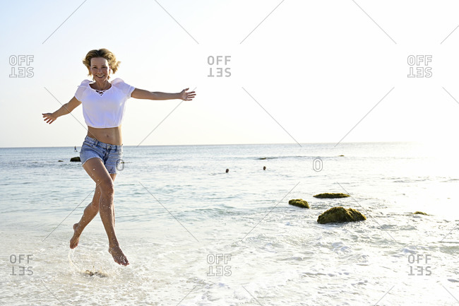 Beautiful woman running and jumping for joy on the beach