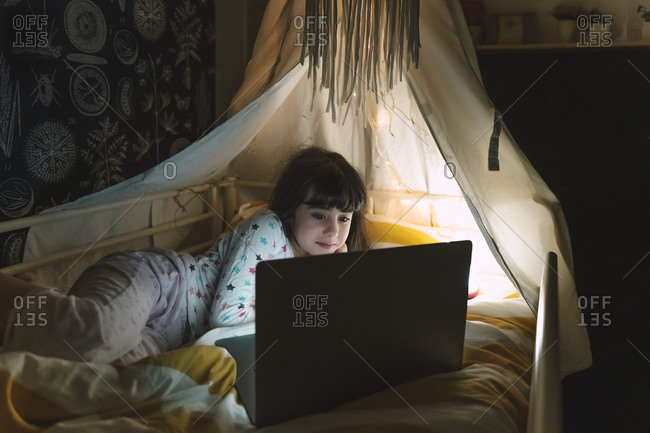 Portrait of girl lying on bed at night looking at laptop