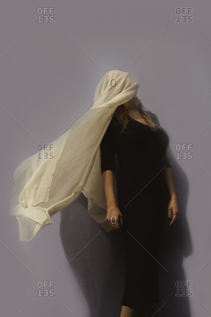 Woman under cloth in front of gray wall