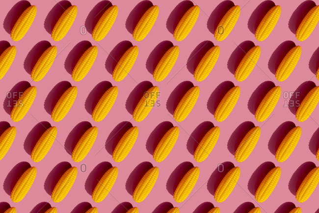 Pattern of yellow plastic corn cobs against pink background