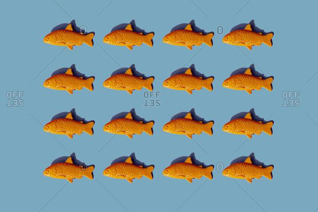 Studio shot of rows of yellow plastic fish