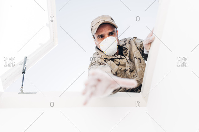 Soldier with face mask on emergency operation- reaching through skylight