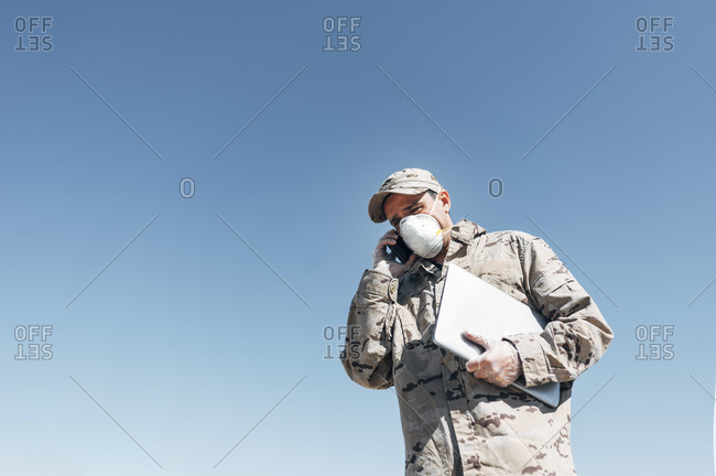 Soldier with face mask on emergency operation- using smartphone- carrying laptop