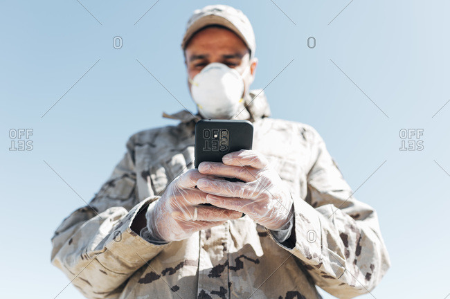Soldier with face mask on emergency operation- using smartphone