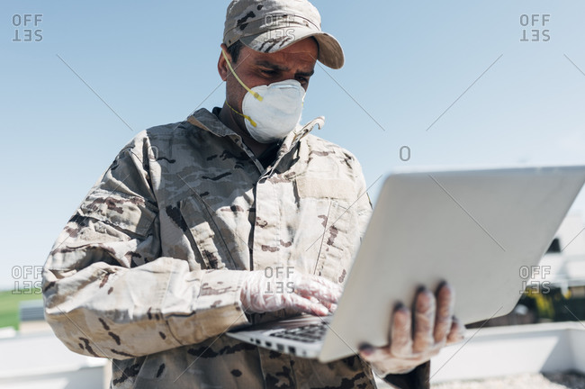 Soldier with face mask on emergency operation- using laptop