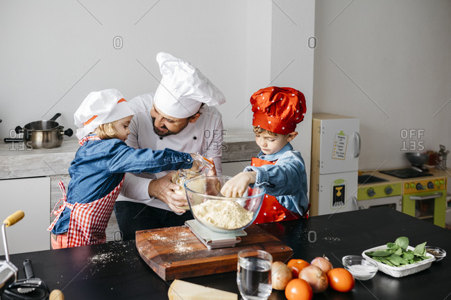 Father with two kids preparing dough for homemade gluten free pasta in kitchen at home