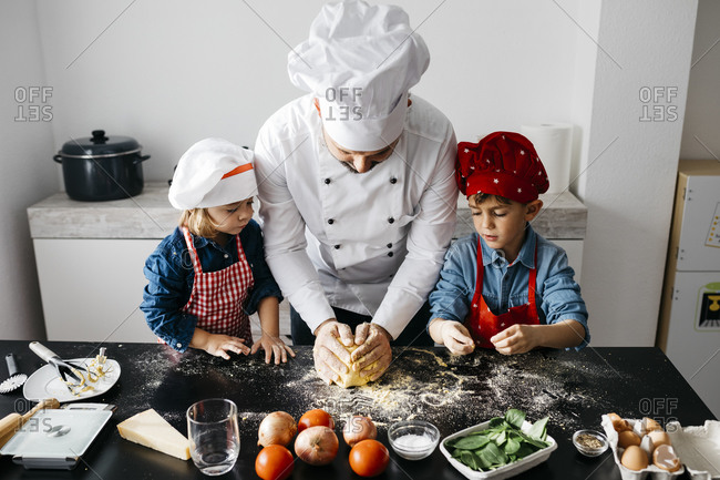 Father with two kids preparing homemade gluten free pasta in kitchen at home
