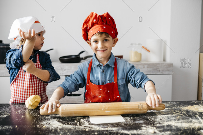 Brother and sister preparing dough in kitchen at home