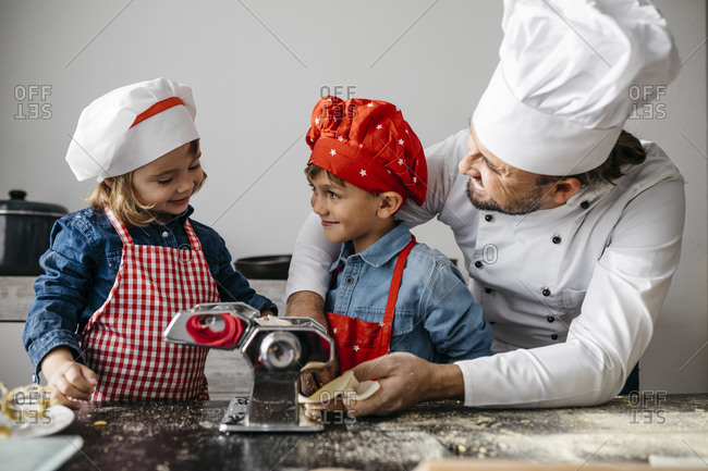 Father with two kids making homemade pasta with pasta machine in kitchen at home