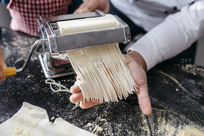 Making homemade pasta with pasta machine in kitchen at home