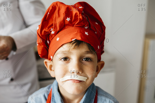 Portrait of playful boy with pasta fake moustache in kitchen at home