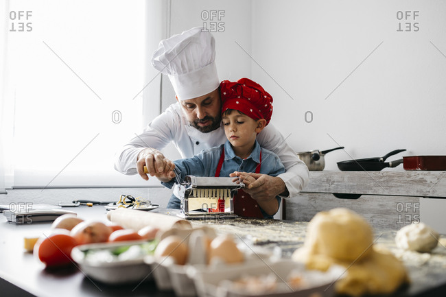 Father and son making homemade pasta with pasta machine in kitchen at home