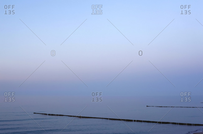 Germany- Mecklenburg-Western Pomerania- Zingst- Clear sky over groynes on Baltic Sea coast at dusk