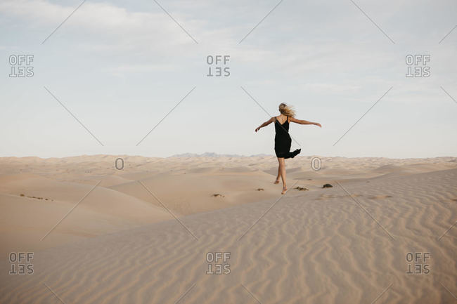 Back view of blond woman jumping in the air- Algodones Dunes- Brawley- USA