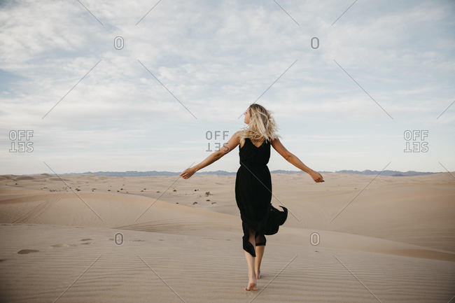 Back view of blond woman walking barefoot on sand dune- Algodones Dunes- Brawley- USA