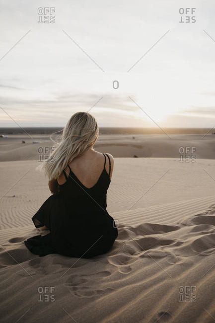 Back view of blond woman sitting on sand dune watching sunset- Algodones Dunes- Brawley- USA