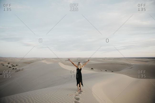 Back view of blond woman standing on sand dune raising hands- Algodones Dunes- Brawley- USA