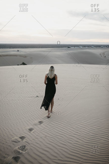 Back view of blond woman walking on sand dune- Algodones Dunes- Brawley- USA