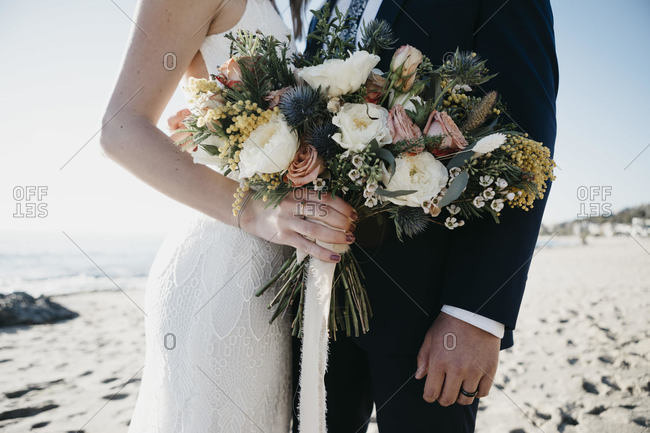 Bridal couple with bridal bouquet at the beach