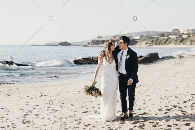 Happy bridal couple walking at the beach