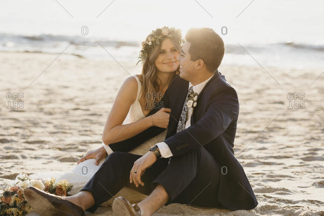Happy bridal couple sitting at the beach