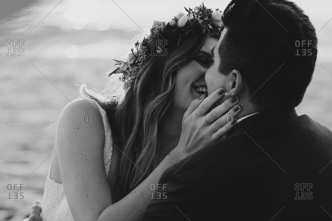 Happy bridal couple kissing each other at the beach- black and white