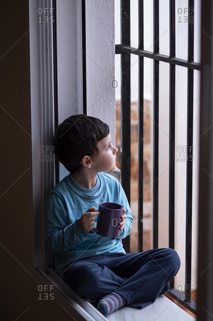 Little boy with mug sitting on window sill looking at distance