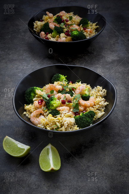 Two bowls of friedbasmatirice with broccoli- shrimps- chili- cilantro- lime and ginger