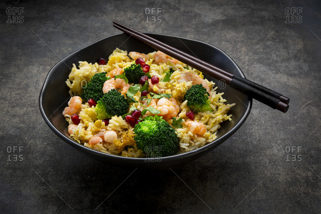 Bowl of friedbasmatirice with broccoli- shrimps- chili- cilantro- lime and ginger