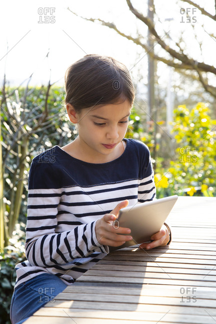 Portrait of little girl sitting at garden table looking at digital tablet