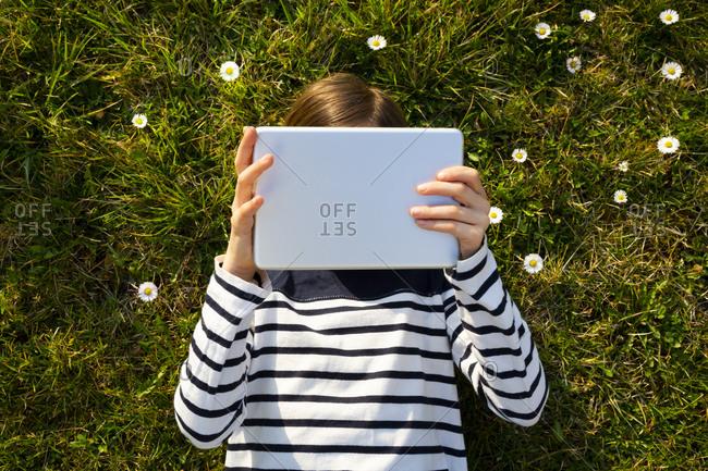 Little girl lying on flower meadow hiding face behind digital tablet