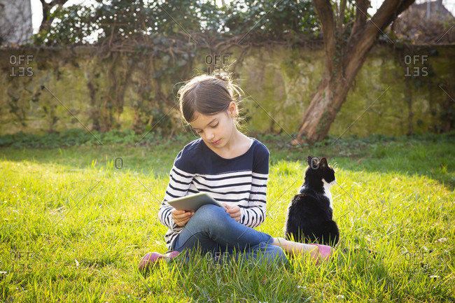 Little girl sitting on a meadow using digital tablet