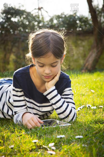 Portrait of little girl lying on a meadow using digital tablet