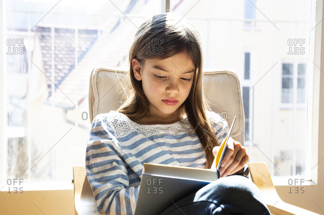 Portrait of girl sitting on armchair reading a book