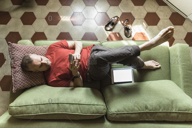Mature man lying on sofa in living room and using tablet