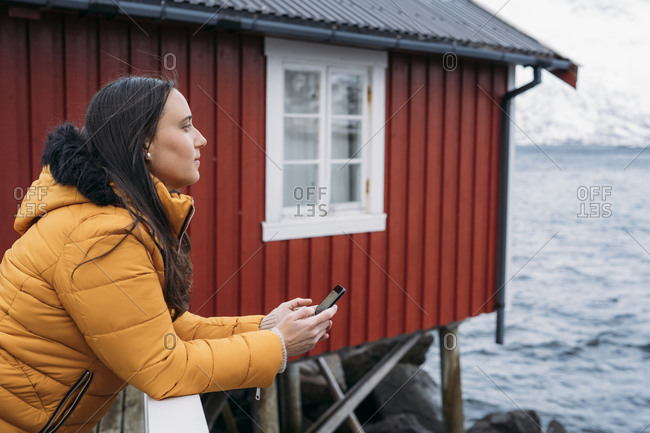 Tourist with cell phone at a hut at the coast- Lofoten- Norway