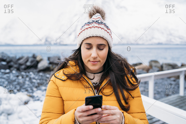 Tourist using cell phone at the coast- Lofoten- Norway