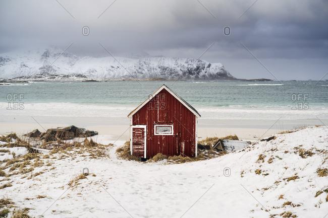 Red hut on the beach in snow- Lofoten- Norway