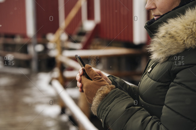 Close-up of woman using cell phone at a hut- Lofoten- Norway