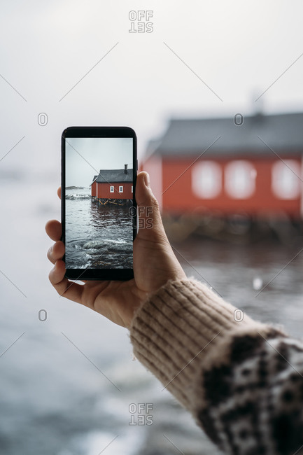 Close-up of tourist taking a cell phone picture of a hut at the coast- Lofoten- Norway