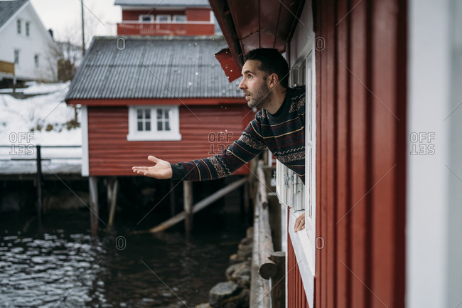 Tourist leaning out of window of a hut- Lofoten- Norway