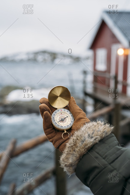 Close-up of hand holding compass at the coast- Lofoten- Norway