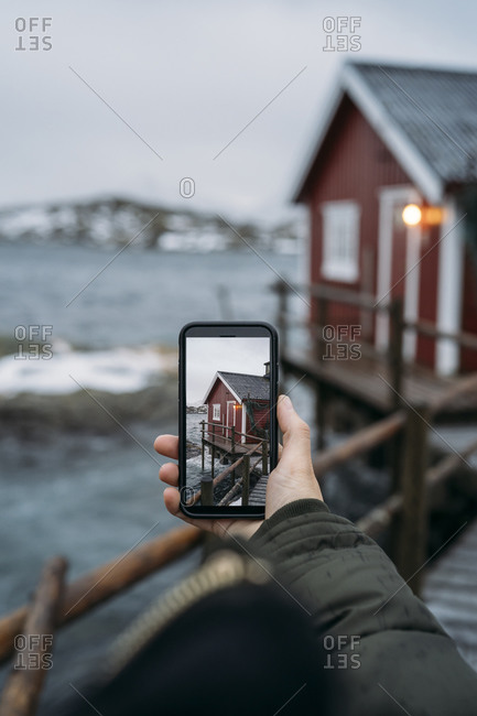 Close-up of tourist taking a cell phone picture at the coast- Lofoten- Norway