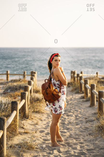Young woman standing at the beach in the evening