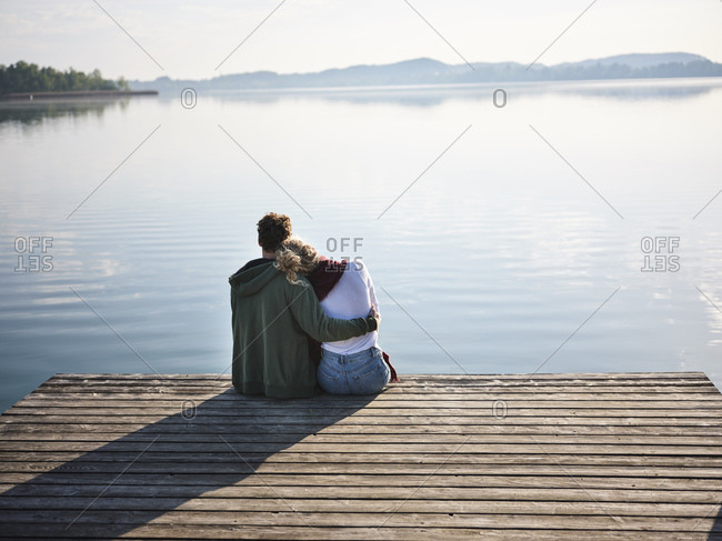 Romantic couple sitting on jetty at the lake