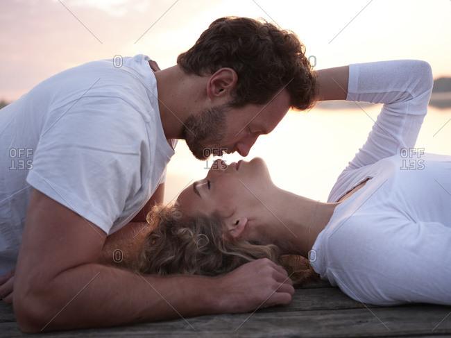Romantic couple lying on jetty- kissing