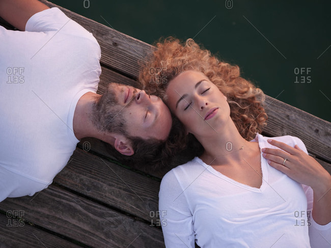 Romantic couple lying on jetty- relaxing