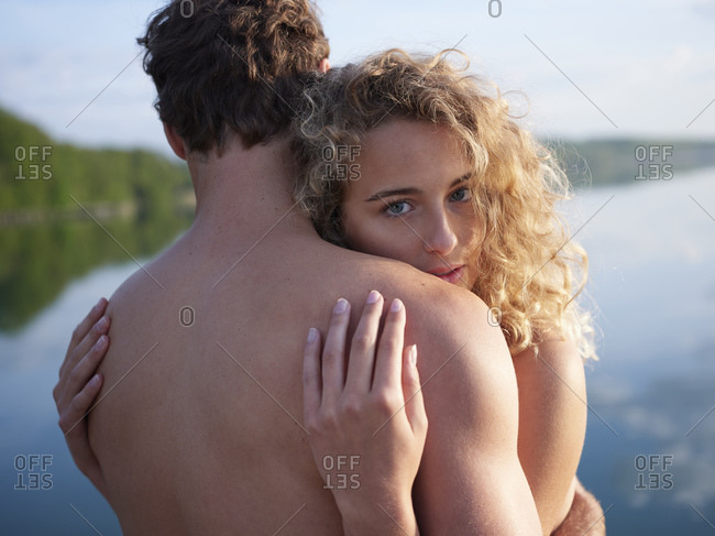 Nude couple embracing in nature- woman looking at camera