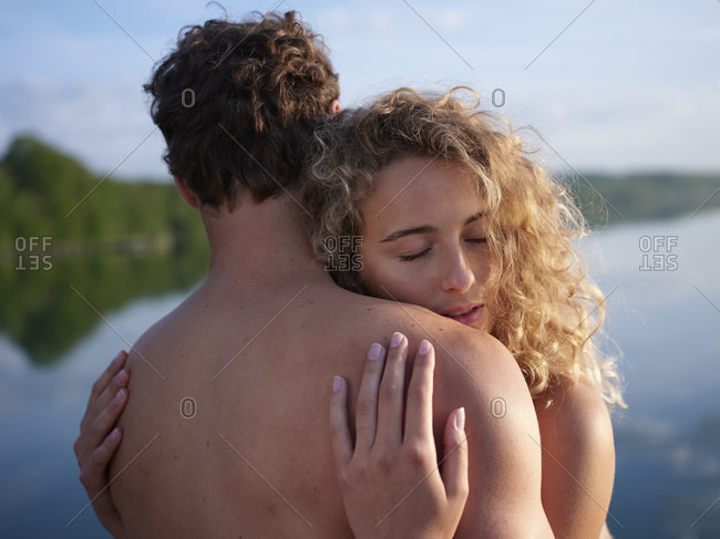 Nude couple embracing in nature
